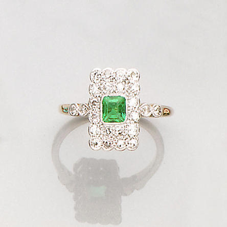 An early 20th century emerald and diamond cluster ring,