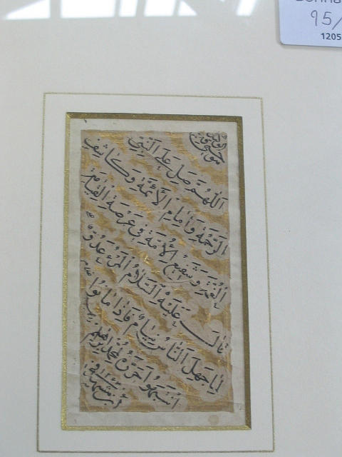 An Arabic calligraphic panel in black ornamental thuluth script with a central rectangle containing the names Fatimah, Imam `Ali, Hasan and Husain (3)
