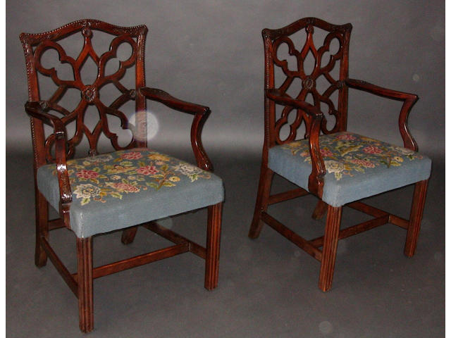 A pair of George III provincial mahogany open arm elbow chairs