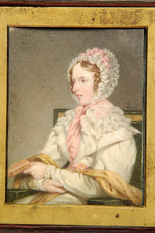 Samuel Lover, R.H.A.(1797-1868) A young lady in near profile, wearing a lace-trimmed bonnet and comforter adorned with pink ribbons, over a white gown and gold coloured shawl, seated and holding a book 115 x 88mm, in gilt metal mount and travelling case.