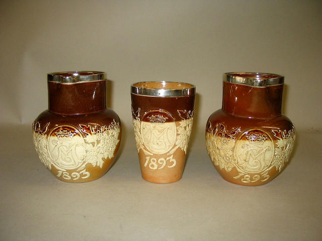 A pair of Doulton Lambeth commemorative jugs and a beaker