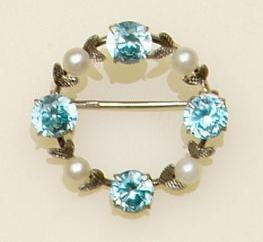 A blue zircon and cultured pearl set circular hoop brooch, spaced with foliate detail, a pearl set bar brooch applied with three flowerheads and an aquamarine set bar brooch, first brooch diamter 2.8cm. (3)