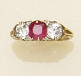 A three stone ruby and diamond ring The central round mixed-cut ruby flanked by two old-brilliant cut diamonds, with diamond points between, claw set in pierced scrollwork mount, ring size J.
