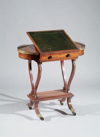 A George IV mahogany games/work table With inset leather writing surface to the adjustable top, revealing a blue leather backgammon surface and a further chequer board slide under, flanked by bowed lidded compartments with gilt metal galleries, on lyre supports, stepped platform, and squat sabre legs terminating with brass paw castors,  77cm wide.