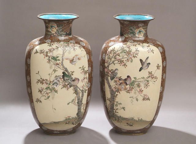 A pair of late 19th Century cloisonne enamel large vases Of flattened ovoid form, each reserving two ivory ground panels decorated with birds on boughs of blossoming trees, on a ground of repeating stylized flowers and foliage highlighted with aventurine, 74cm high. (2)