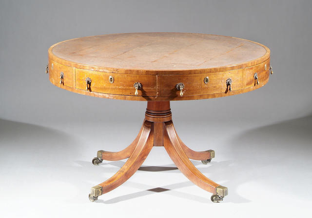 A George III mahogany drum table With leather lined top and fitted with four frieze drawers flanked by dummies, on turned column and quadruple splayed legs and brass capped castors, 114cm diameter.