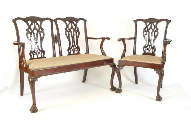 A Chippendale style carved mahogany twin chairback settee and a pair of elbow chairs by Baker of Bath