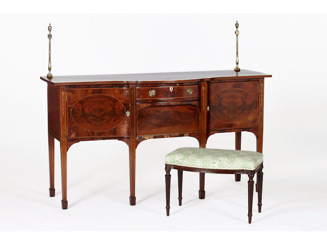 An Edwardian mahogany inlaid serpentine sideboard with brass gallery rail supports and satinwood banded top,