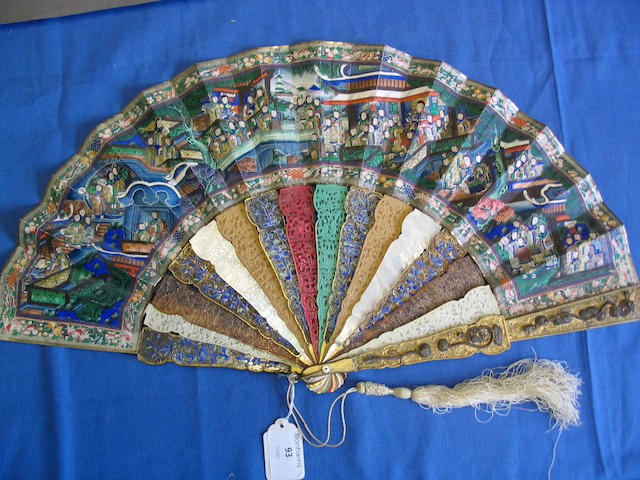 A good early 19th Century Chinese export fan The guards in gilded metal overlaid with silver wirework dragons and motifs, the sticks in alternating materials, gilded metal, ivory tortoiseshell, sandalwood and mother-of-pearl, some colour stained, the leaves painted to each side with numerous ivory faced courtiers arranged in terraces, on bridges and other defined areas within a floral, bird, fish and animal border, 29cm.