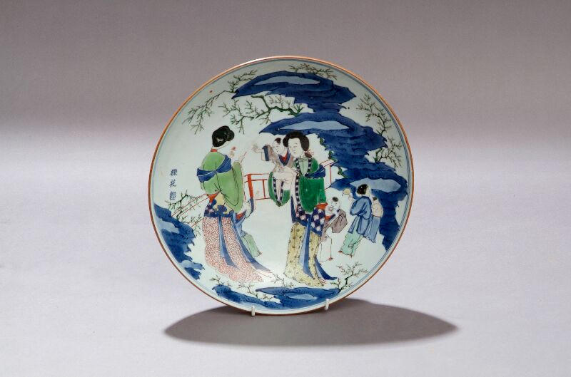 A Transitional saucer dish Decorated with court ladies and attendants in a garden in yellow, green, iron red and underglaze blue and incorporating three character inscription, 30cm diameter.