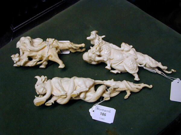 Three Japanese carved ivory groups of animals A rhinocerous being attacked by two tigers, 18cm long, a bull and a calf being attacked by a python, 21.5cm long and an elephant being attacked by two tigers, 14cm long. (3)