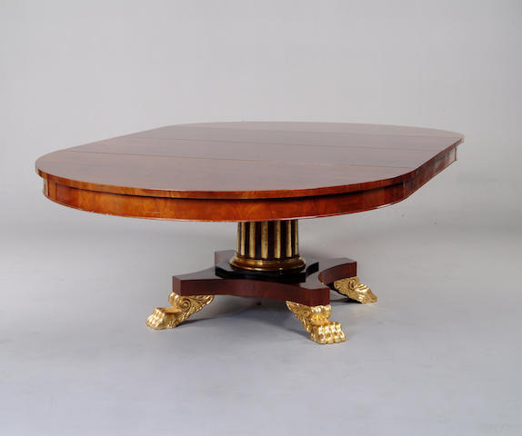 A Baltic Empire style mahogany and parcel gilt extending dining table