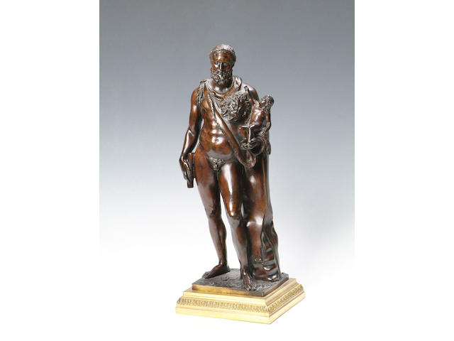 A late 19th Century French bronze group of Hercules Standing, naked with a lions skin cloak and holding a young child on his left arm, on a gilt metal base, 42cm high.