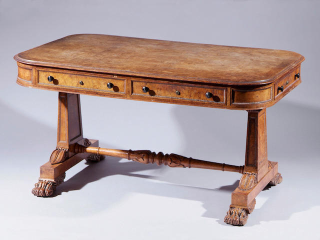 A George IV pollard oak library table With moulded edge, the frieze with two drawers either side and also a drawer to either end, on panelled and split bobbin decorated end supports united by a turned stretcher, on paw feet, 142 x 91cm.