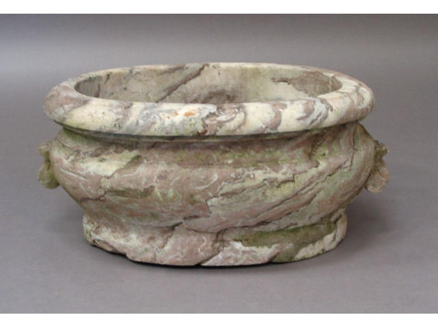 An 18th Century or earlier weathered and variegated rouge marble oval cistern