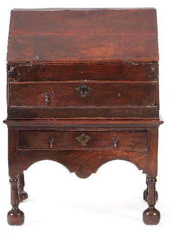 An early 18th Century oak bureau on stand,