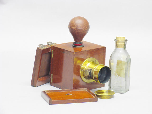 "Dubroni No. 2 camera by A. Bourdin France; patented May 21 1860, for images 4.5 x 5.5cm polished wood and brass body, red glass viewing window, internal ceramic developing chamber, ground glass, maker's plate: ""Appareil Dubroni Brevete SCDG A Paris 256 Rue de Rivoli"", a brass bound lens engraved ""Darlot Paris"" with cap, pipette with rubber bulb, tripod platform, printing frame and bottle impressed ""Dubroni""  (7)"