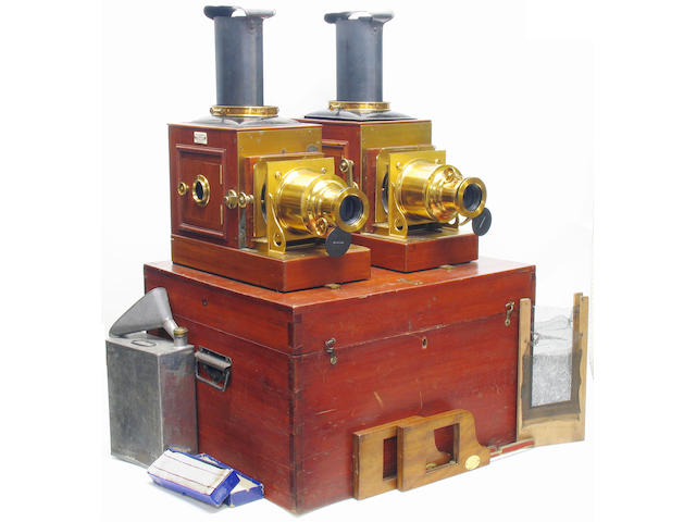 "New Pamphengos Twin Lantern set,  W. C. Hughes London; matching mahogany bodied magic lanterns each with  lacquered brass fittings and black finished metal lamphouse tops, W. C. Hughes lacquered brass cased projection lenses, condensers, side opening lamphouse doors, W. C. Hughes patent Pamphengos spirit burners with reflectors and chimneys, each lantern labelled ""W. C. Hughes Patentee Brewster House Mortimer Rd Kingsland London N""; metal spirit canister, funnel, spare wick, and fine net panels,"