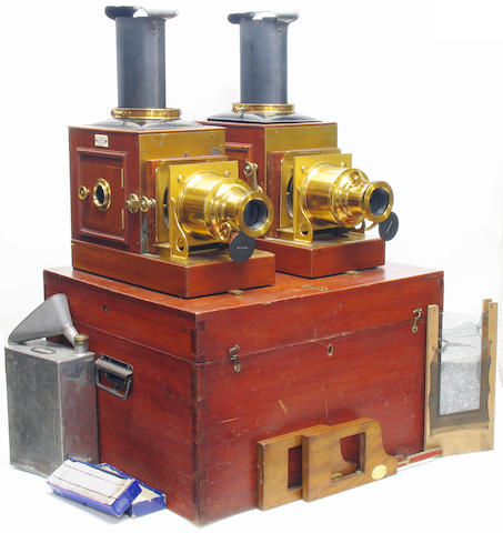 """New Pamphengos Twin Lantern set,  W. C. Hughes London; matching mahogany bodied magic lanterns each with  lacquered brass fittings and black finished metal lamphouse tops, W. C. Hughes lacquered brass cased projection lenses, condensers, side opening lamphouse doors, W. C. Hughes patent Pamphengos spirit burners with reflectors and chimneys, each lantern labelled """"W. C. Hughes Patentee Brewster House Mortimer Rd Kingsland London N""""; metal spirit canister, funnel, spare wick, and fine net panels,"""