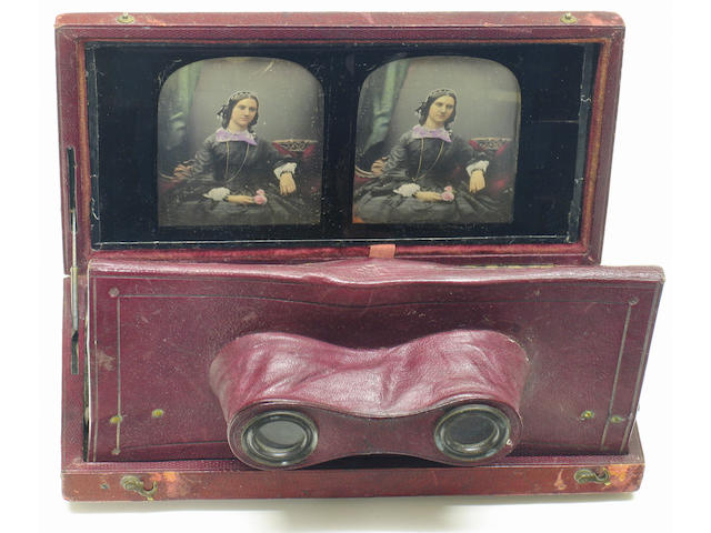 "Antoine Claudet Stereo Daguerreotype Stereoscopic daguerreotype of a seated lady holding a rose in Claudet's gilt crested red leather folding stereo viewing case; mid to late 1850's with label on reverse of backing paper with Claudet's information and the address ""107 Regent Street"" . A finely tinted and gilded example of a charming subject, Claudet is most known today for his fine portraits.Note; Claudet patented his viewing case March 23 1853. The views can be removed by pulling on a ribbon i"