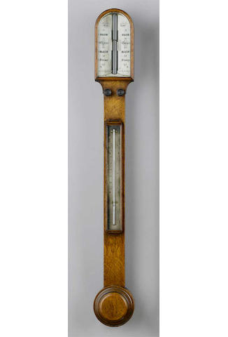 A late 19th Century oak stick barometer, Carpenter & Westley, 24 Regent St. London, arched hood over a slim trunk with twin recording knobs, mercury thermometer and flat fronted turned cistern cover, twin ivory angled dials with verniers, 93cms high.