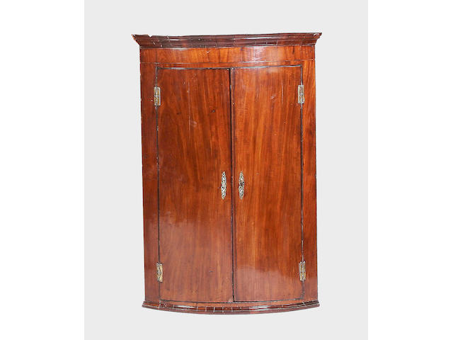 A George III mahogany bow-fronted hanging corner cupboard,
