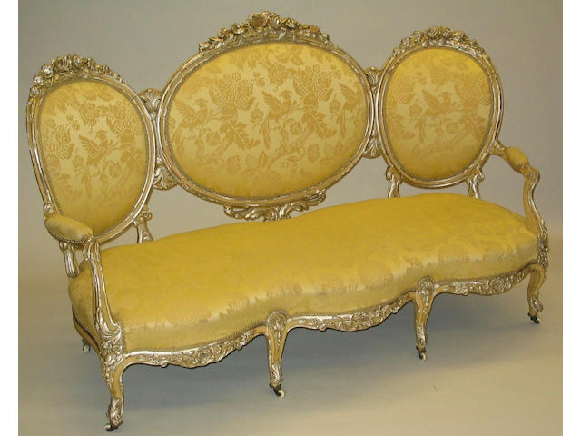 A mid-19th Century Louis XV style cream and silvered, carved beech frame upholstered settee