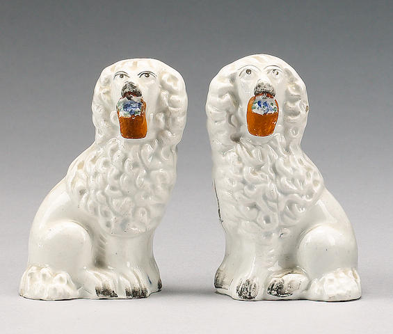 A pair of small spaniels with baskets of flowers in their mouths, circa 1860,