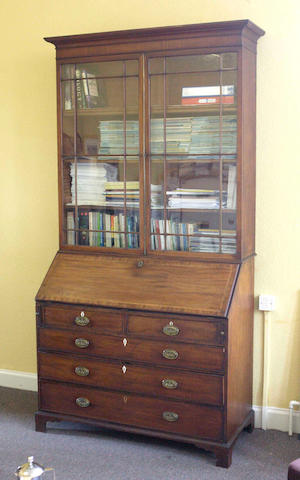 A George III mahogany and inlaid bureau with a later bookcase top,