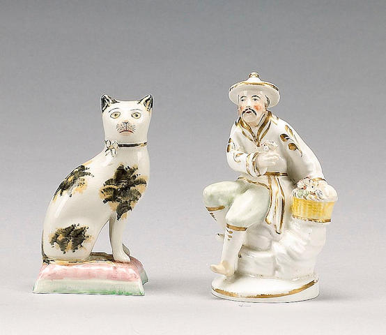 A model of a cat on a cushion, and a Staffordshire porcelain figure of a China man, circa 1900 and 1840,