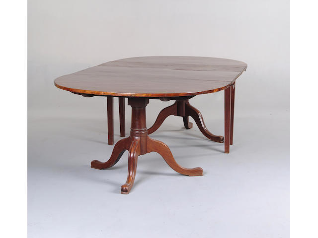A George IV mahogany twin pillar dining table with drop leaf centre section
