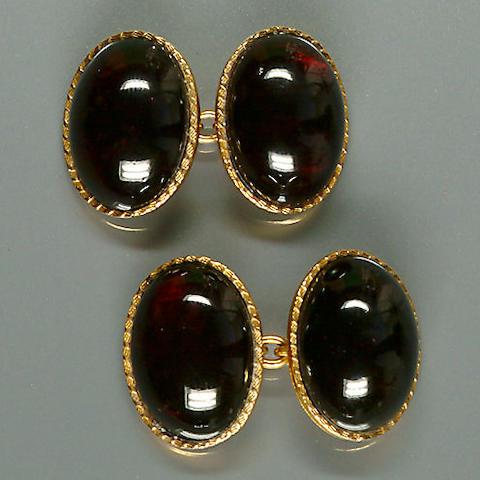 50513300006 A pair of oval-cut cabochon garnet cufflinks