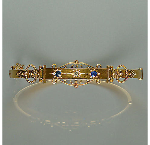 50302240001 An early 20th century diamond and sapphire-set 15ct. gold bangle