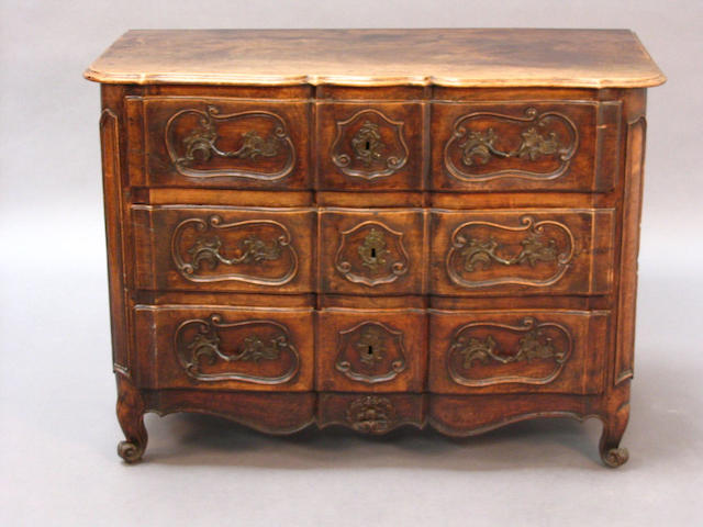 An 18th century French provincial walnut commode of shaped outline
