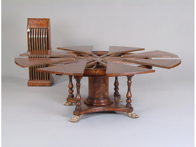 A mahogany and rosewood crossbanded extending circular dining table in the manner of Robert Jupe
