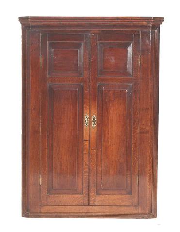 A George III oak wall mounted corner cupboard