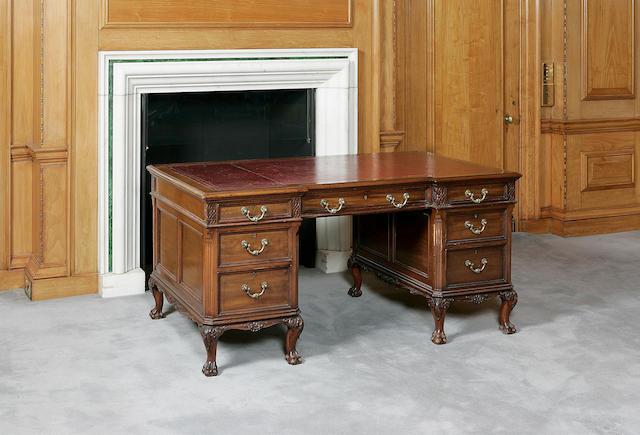 An early 20th century mahogany inverse breakfront pedestal desk