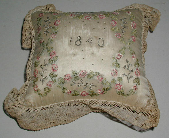 An embroidered and pin stuck pincushion