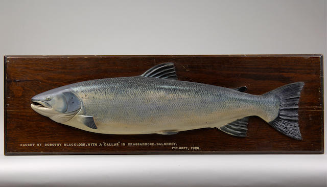 A carved and painted half block salmon