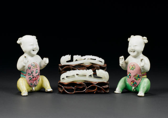Two famille rose seated boys, and two jade belthooks Late 18th/19th century