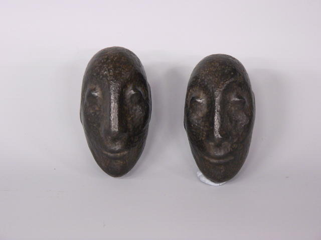 A pair of modern stylised bronze figure of heads