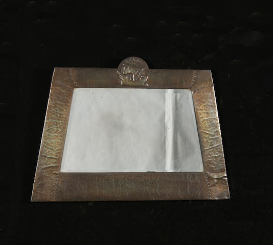 An Arts and Crafts beaten metal framed bevelled wall mirror, with galleon crest and tapered sides, 90cm wide x 64cm high.