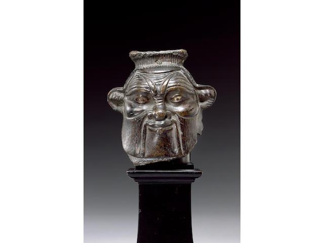 An Egyptian bronze head of Bes