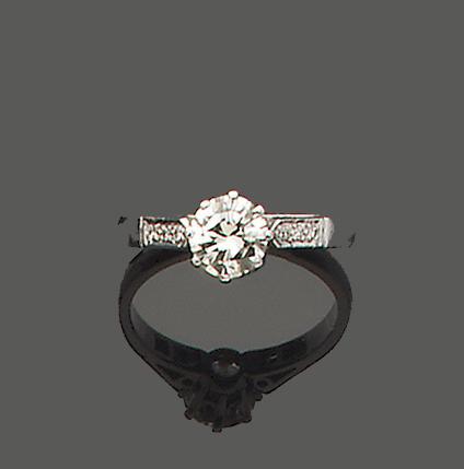 A diamond single-stone ring with diamond-set shoulders