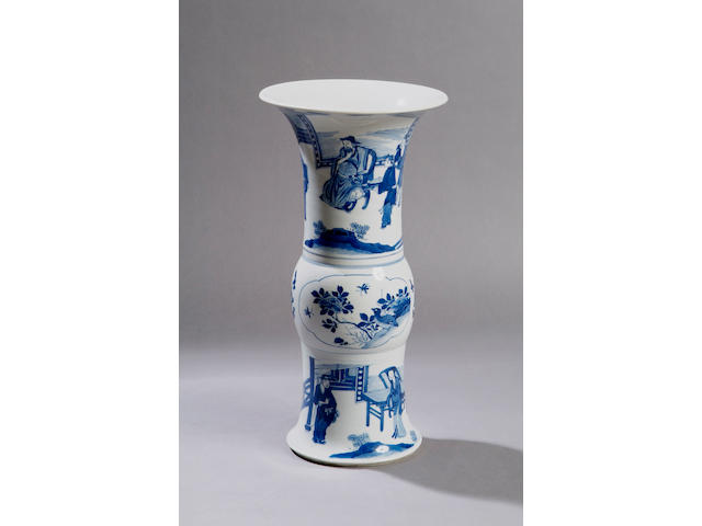 A Kangxi blue and white gu shaped vase Decorated with a continuous scene of figures on a terrace, 44.5cm high.