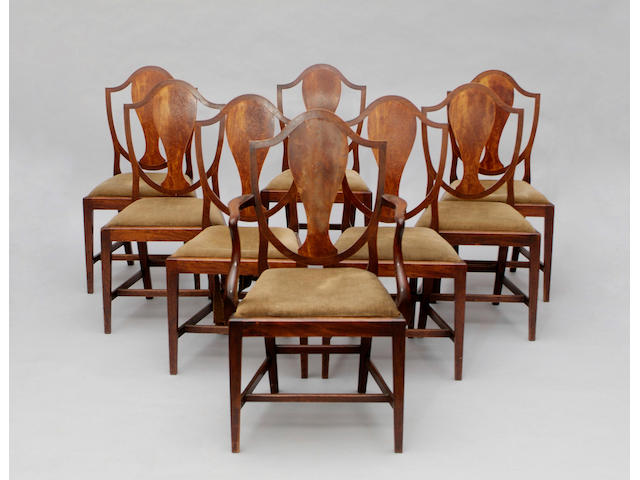 A set of eight mahogany dining chairs The shield shaped backs with solid figured splats, having drop-in seats, on tapering legs (to include one carver). (8)