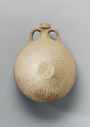 A moulded unglazed pottery Flask Persia, 13th/ 14th Century