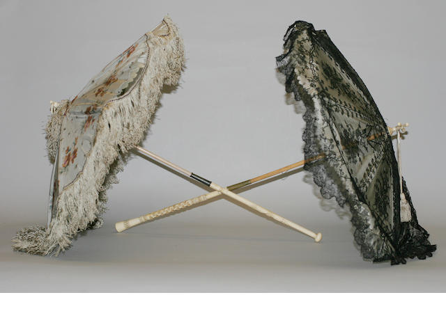 Two mid Victorian parasols The first having a black chantilly overlay and ivory silk shade to folding wooden an ivory handle with decorative carving and cross shaped finial, (probably a mourning parasol), 64cm long, (splits to shade). the second having a dove grey floral shade with fringing to a wooden and ivory folding handle carved with floral and foliate design and looped finial, 60cm long, (shade a.f.). (2)