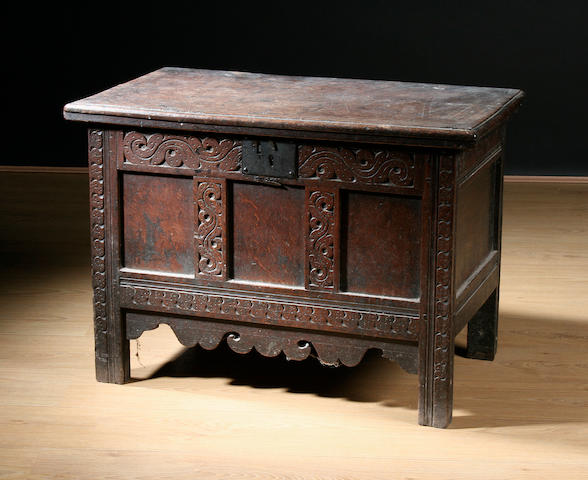 A late 17th Century paneled oak coffer, carved with scrolled decoration shaped apron, 76.5cm