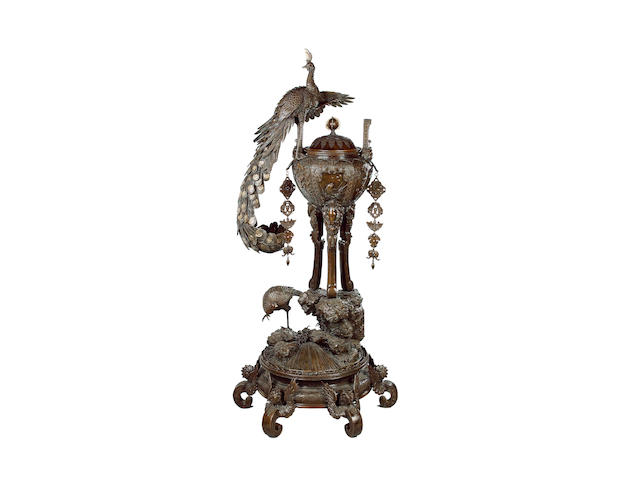 An impressive bronze koro with domed cover, knop finial and an enormous peacock appliqué;